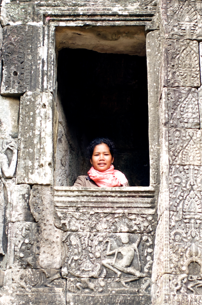 "Guard at Bayon. With carved female ""Apsara"" figure below."