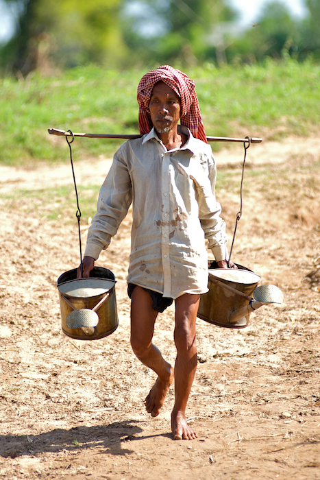 Older man with water cans.
